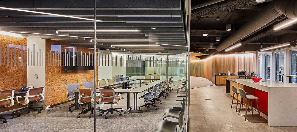 open office space with a conference room surrounded in glass, no ceiling, acoustic linear blades inside.