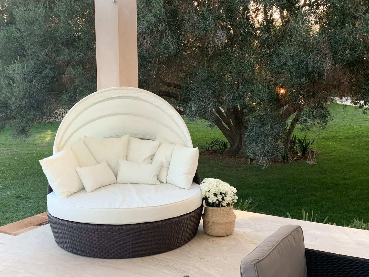 Daybed on terrace under sun sail shade