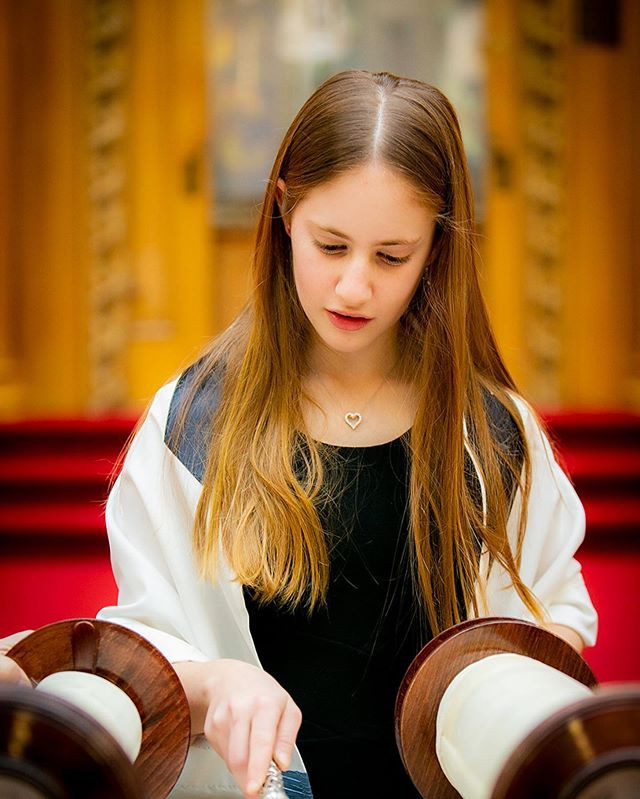 teenage girl reading torah at her bat mitzvah