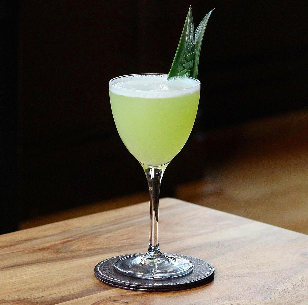 Lime green rum Martini garnished with pineapple fronds, cocktail recipes with rum, summer cocktail recipes, unusual cocktail ingredients