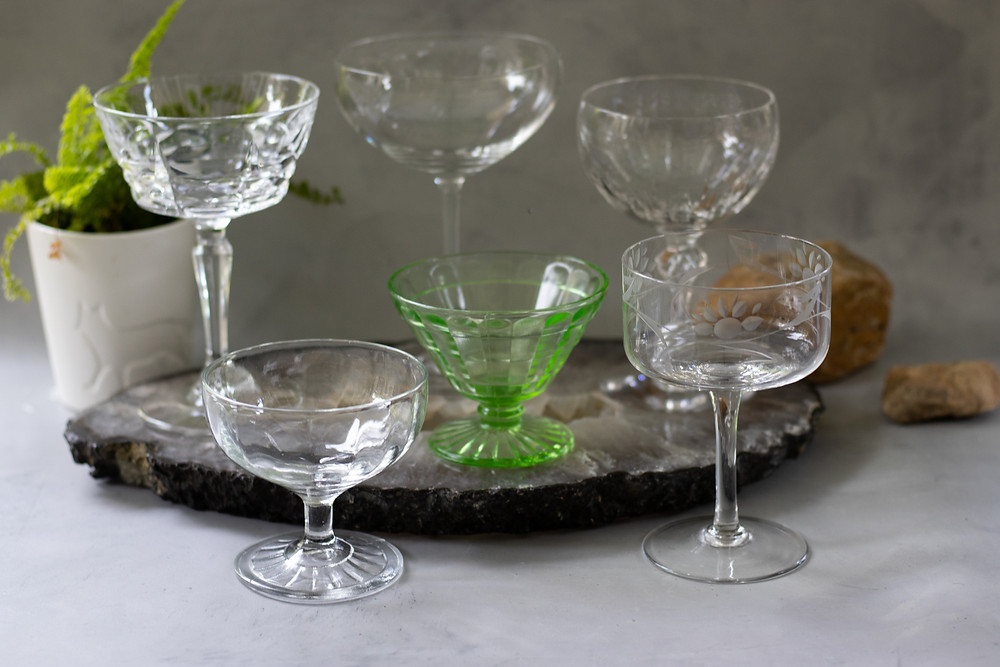 an assortment of cocktail coupe glasses, glasses that invoke a great gatsby vibe, glasses to take the place of flutes, alternatives to flutes, glassware for serving champagne or bubbly, martini glasses, what glassware to serve a martini in, best glassware for a martini manhattan and drinks served up, gimlet, boulevardier