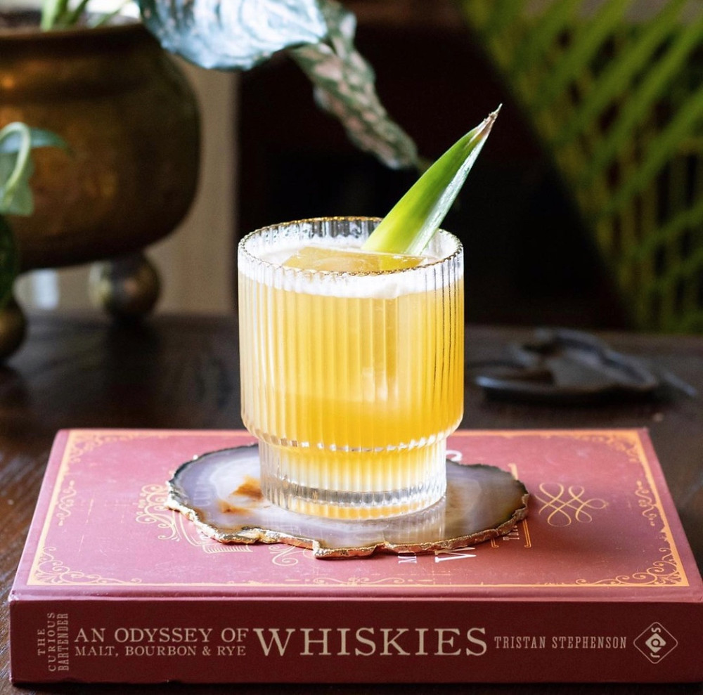 Amber-colored bourbon cocktail garnished with a pineapple frond, easy cocktail recipes, best drinks to make at home, cocktail recipes with bourbon
