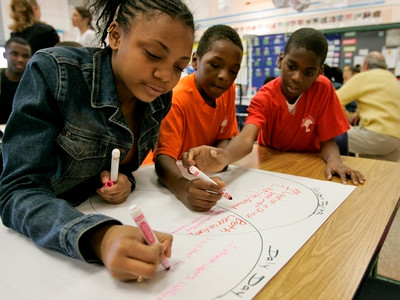 black kids working together on a project in a school classroom, are people of color affected by COVID-19 more than white people