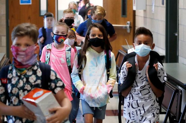 Elementary school students in masks in the hallway at school, attending school during a pandemic
