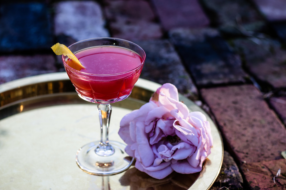 a garnet-colored cocktail served in an antique cocktail coupe and garnished with a pink peony and a lemon twist, the must-have ingredients and tools for making cocktails at home
