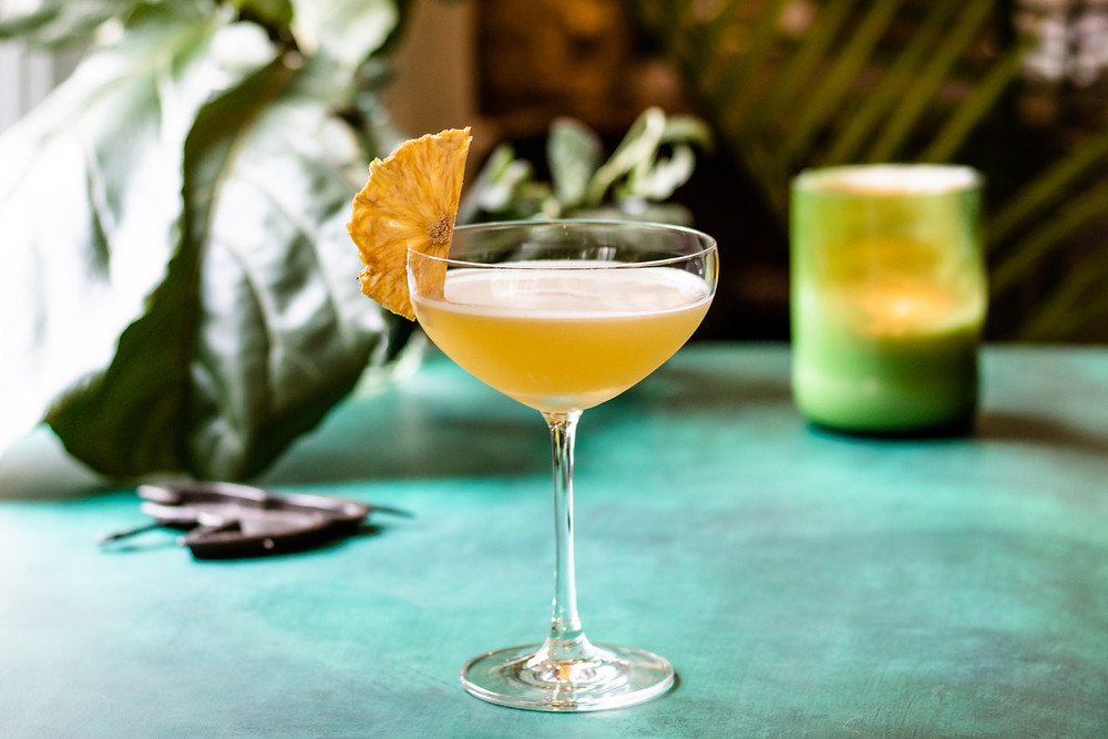 an orange-colored cocktail in a coupe glass that is garnished with a dehydrated pineapple, the essential tools garnishes and mixers for your home bar