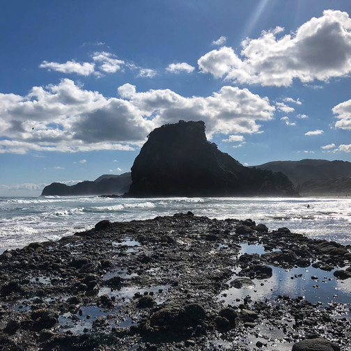 photos of black sand beaches, blue skies and white clouds on the rocky beach at piha overlooking lion rock