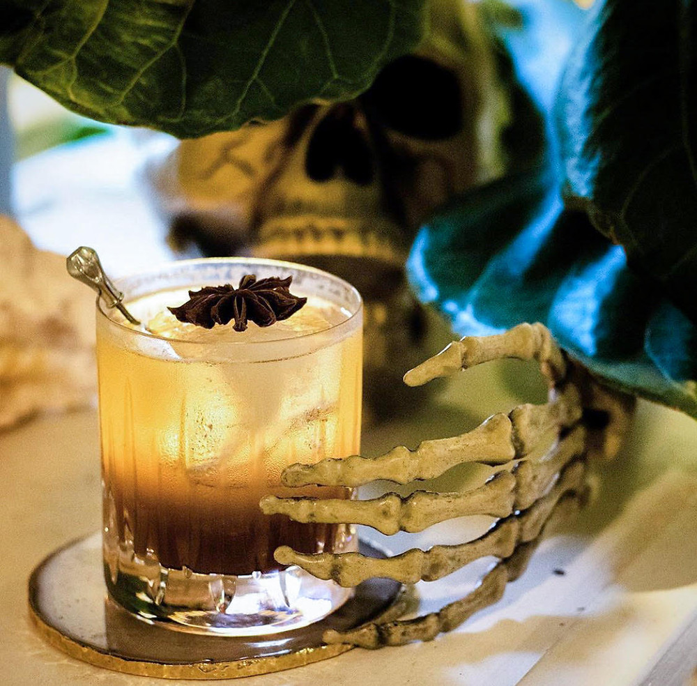 Rum cocktail made with apple butter and a skeleton hand holding it, rum cocktail recipes, best Halloween libations, easy Halloween cocktails