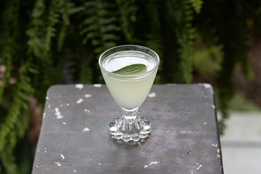 gin gimlet in an antique glas garnished with a sage leaf, cocktails to make using gin, bombay saphire, dry gin, empress 1908, highclere castle