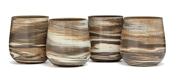 a set of four ceramic wine glasses made with three different colors of clay