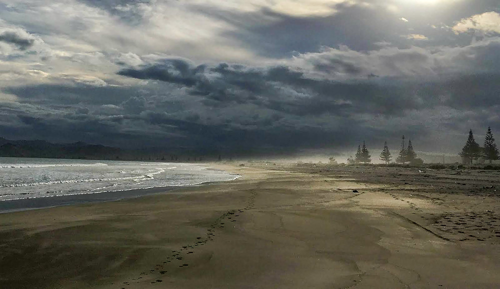 walking on the beach in Gisborne North Island New Zealand at sunset with cloudy skies and a storm rolling in, on the beach, South Pacific, discover golden sand beach of New Zealand, travel new zealand, travel the world, explore north island