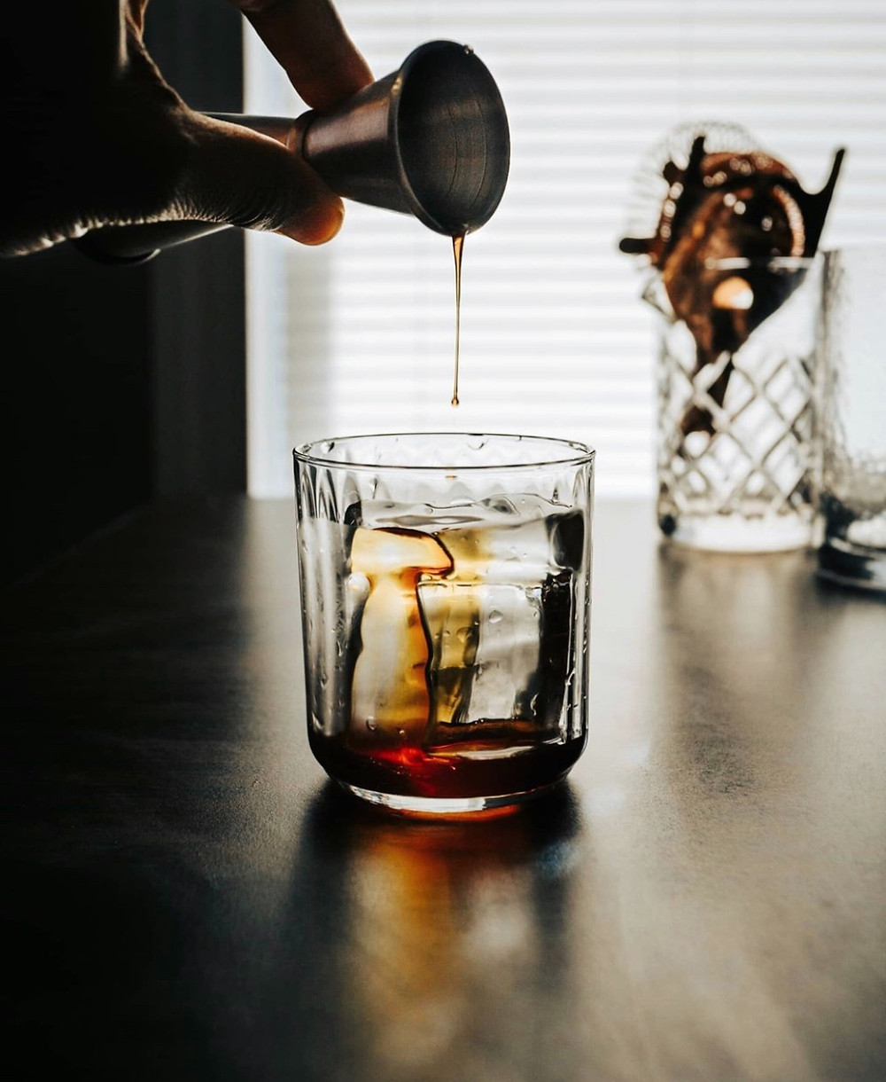 A back-lit gin old fashioned with a jigger pouring simple syrup on the top, old fashioned recipe, old fashioned drink, best cocktails
