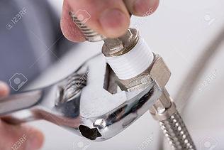 46185067-plumber-screwing-plumbing-fitti