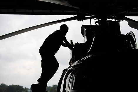 Aircraft mechanic, black and white  ,  Male pilot checks the tail of helicopter before the flight.jp