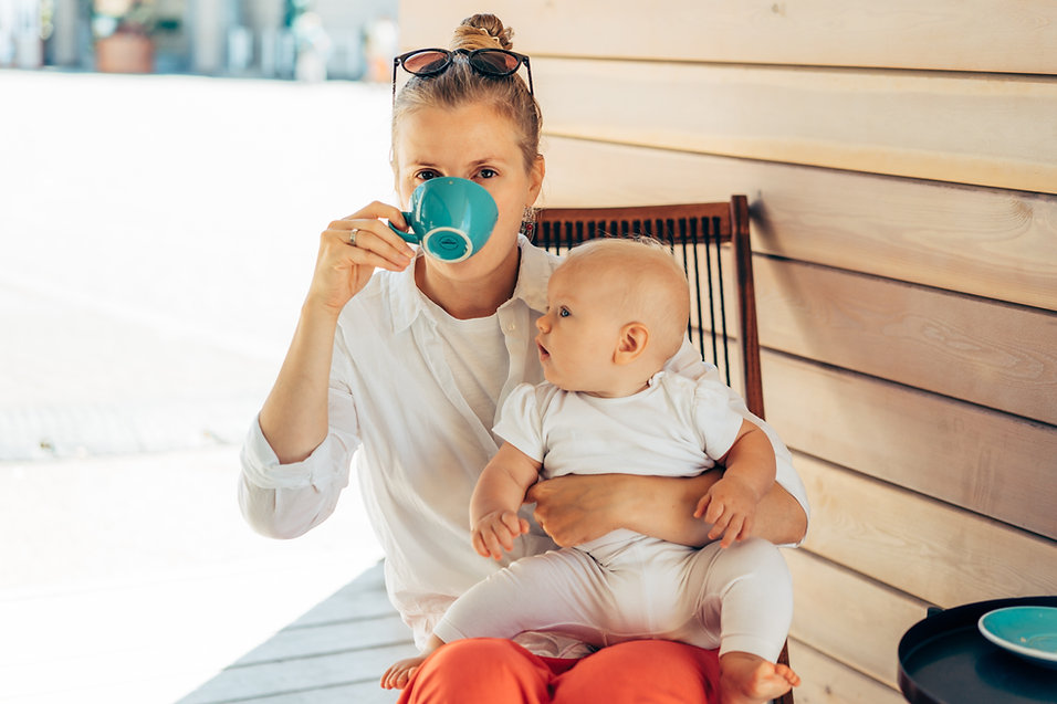 woman-with-a-baby-in-her-hands-drinking-