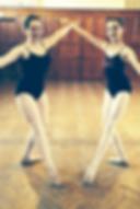 Two ballet dancers posing in dance studio