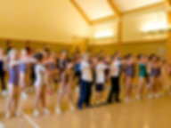 Dancers lined up practicing together in studio