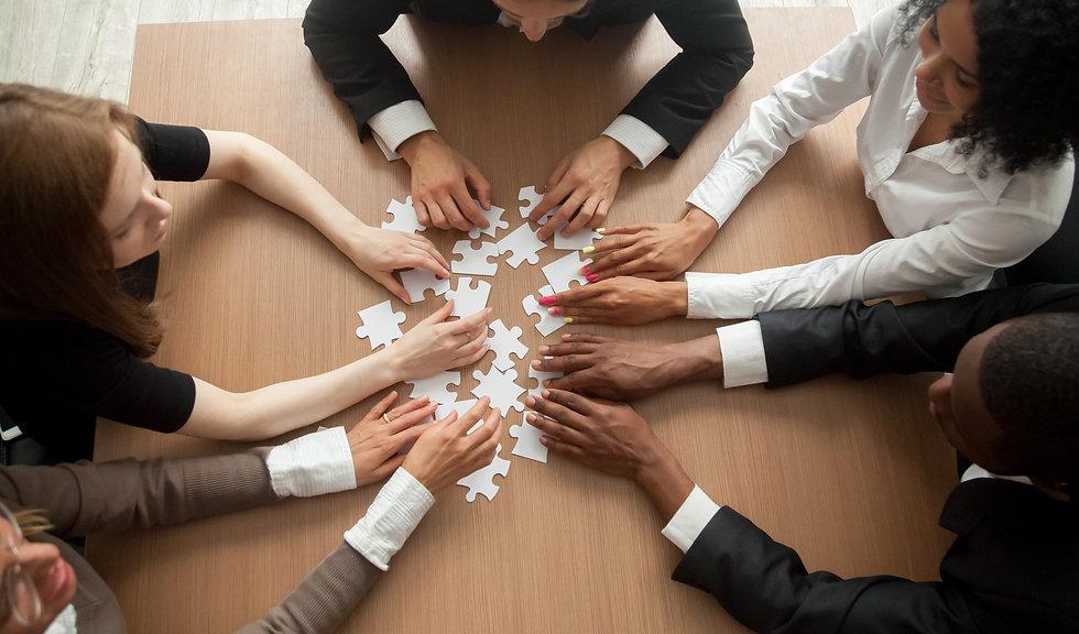 Diverse team people assembling jigsaw pu