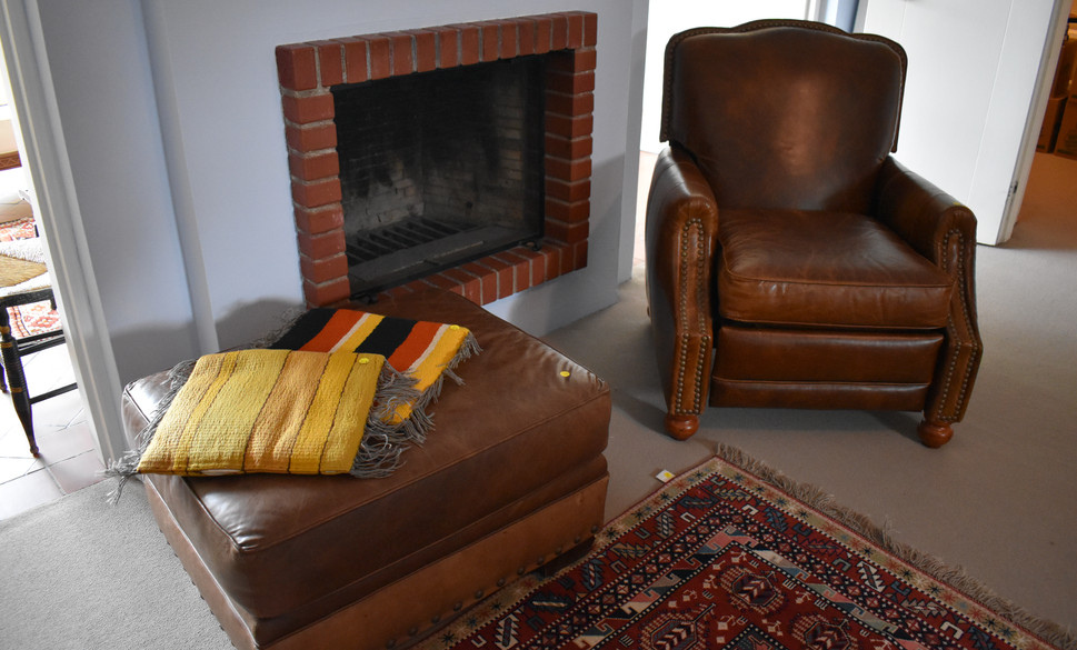 The brown leather chair is a recliner.