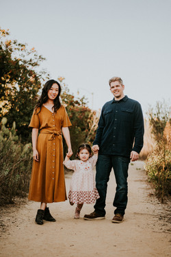family holding hands in a park during the fall family photography los angeles california