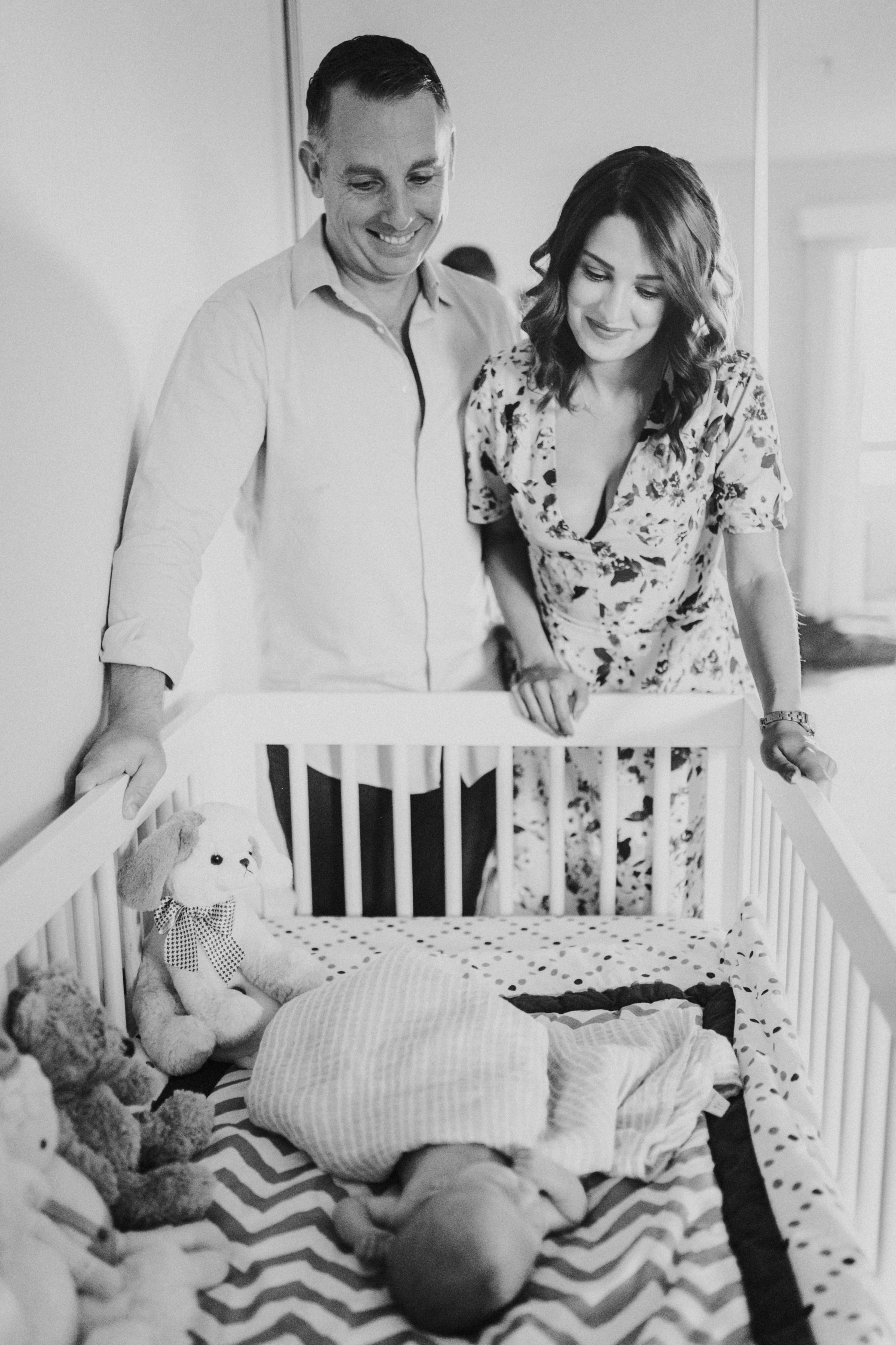 couple looking at baby in crib at home lifestyle newborn photography los angeles california