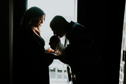 dad kissing baby on forehead silhouette at home lifestyle newborn photography los angeles california