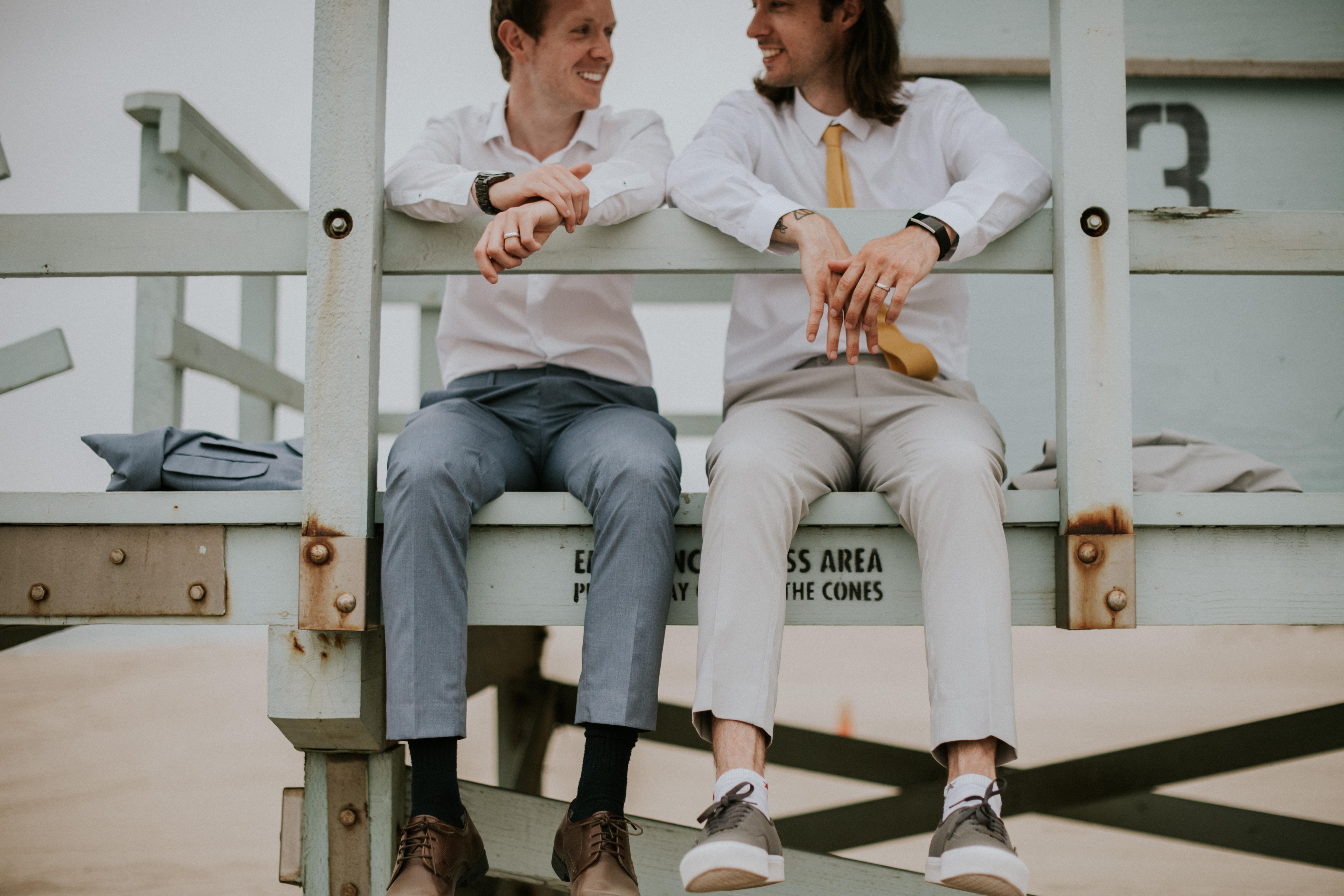 groom and groom posed on beach lifeguard tower gay wedding photography point dume beach malibu calif