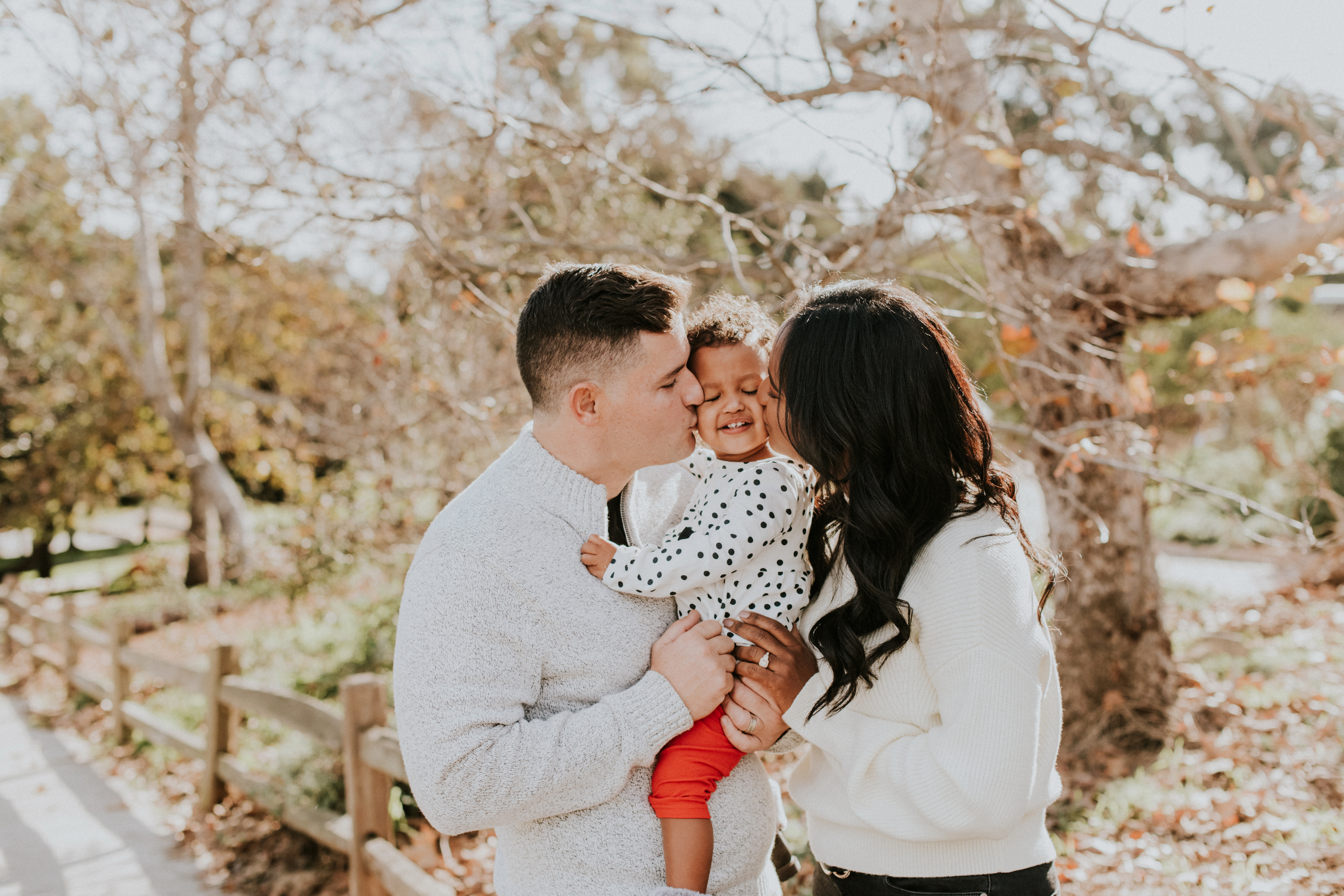 mom and dad kissing child in park christmas holiday photo family photography los angeles california