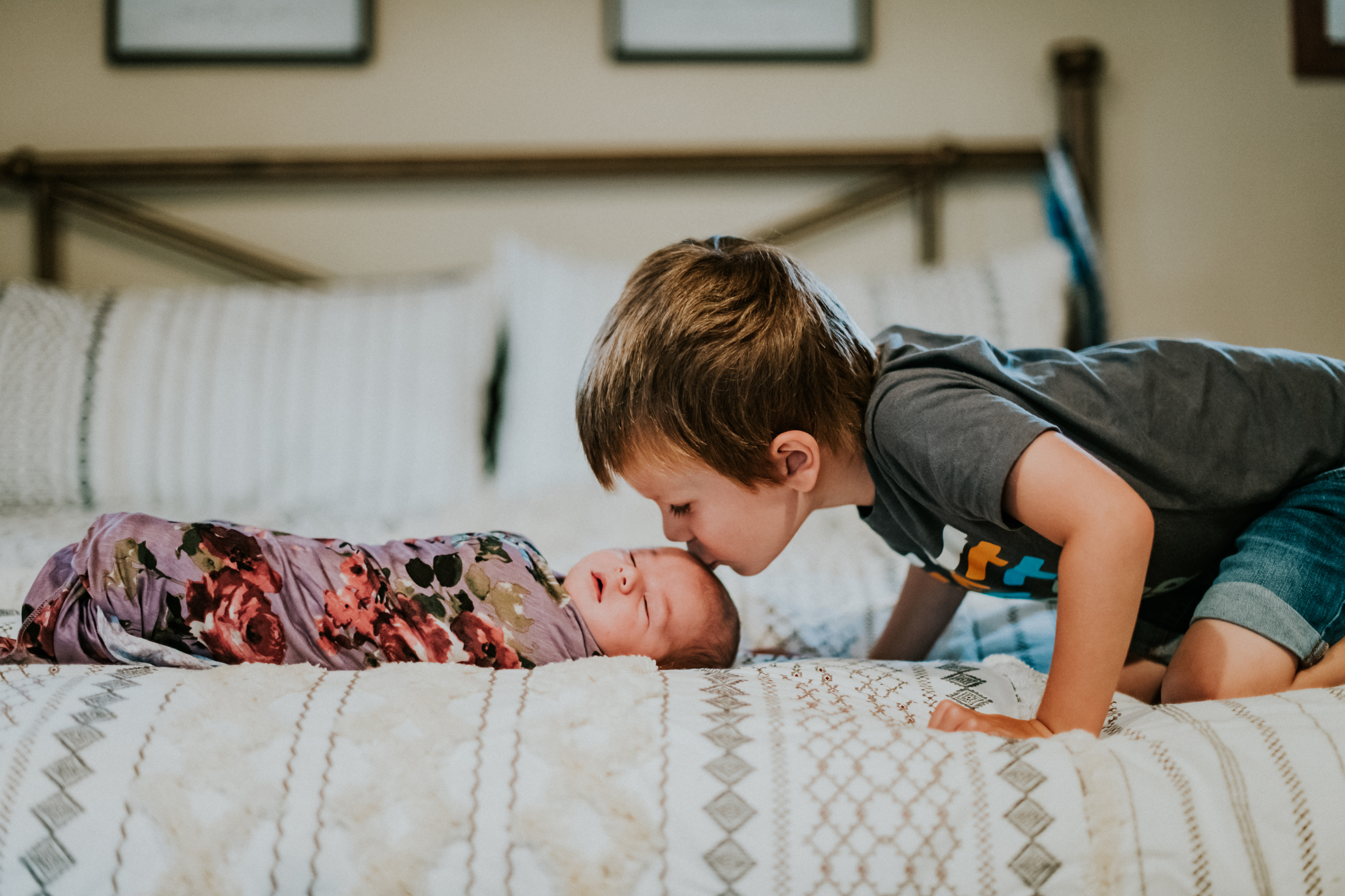 brother kissing baby sister at home lifestyle newborn photography los angeles california