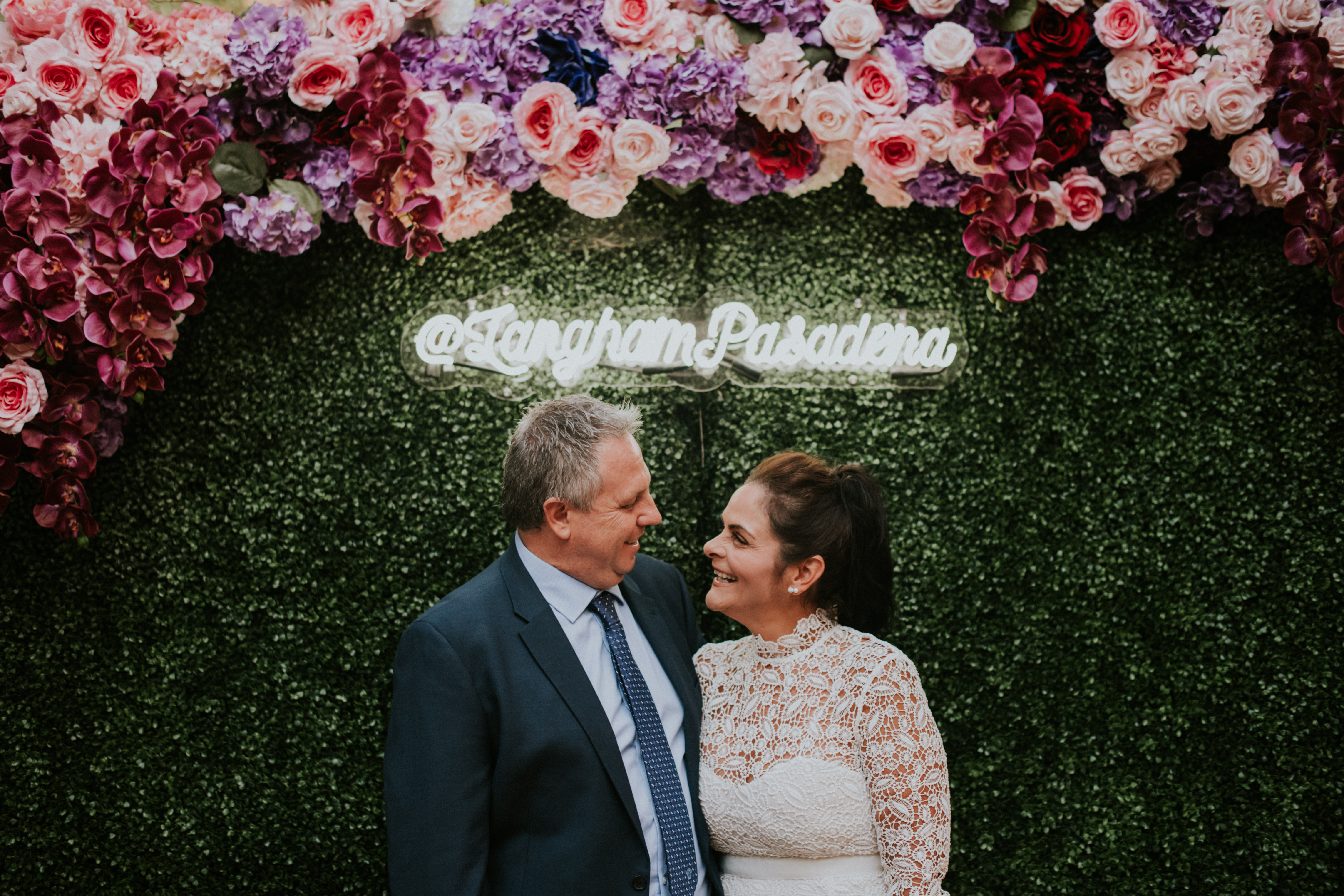 bride and groom posed in front of flower wall wedding day photography at the langham pasadena califo