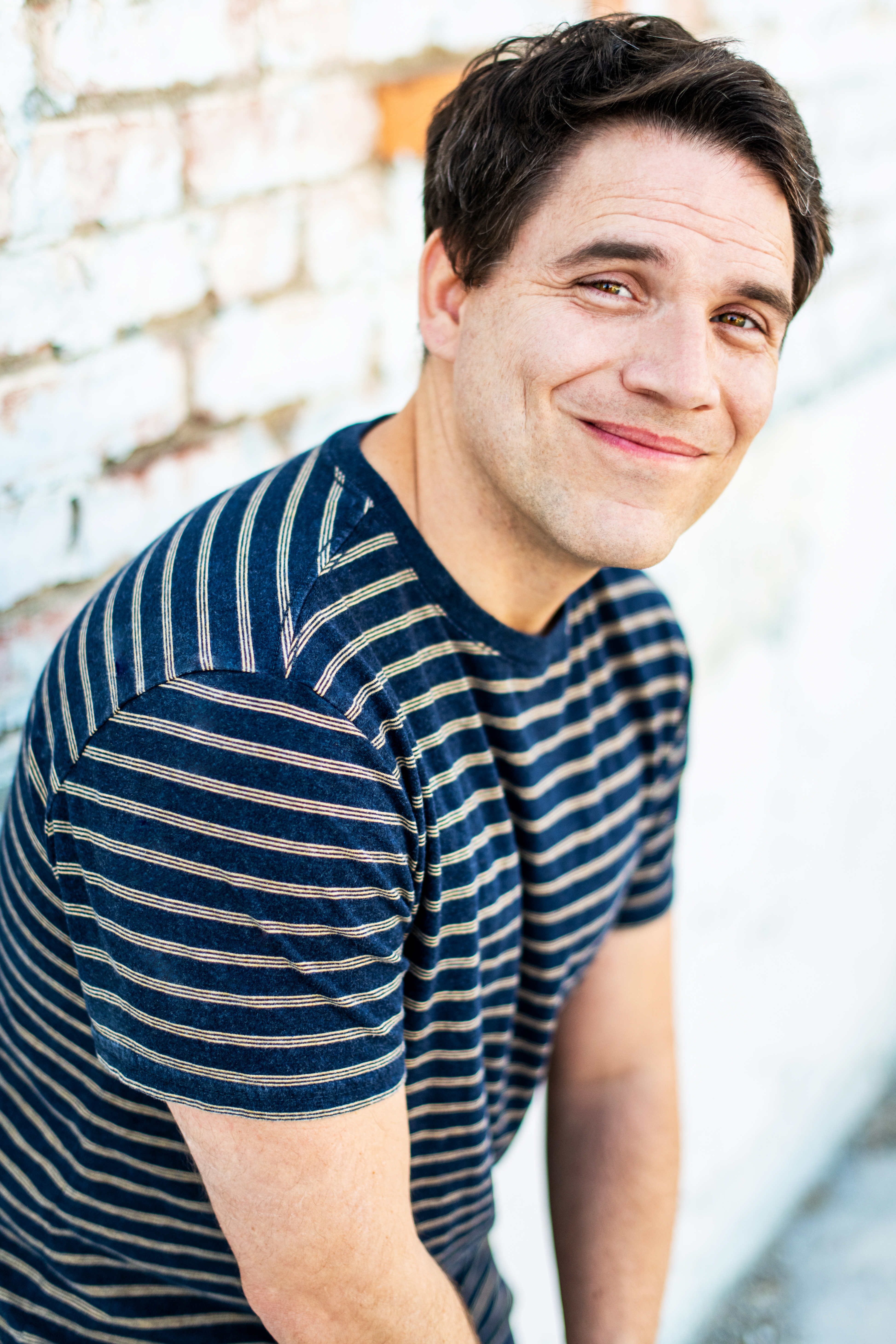 los angeles theatrical commercial headshot for male comedy actor striped t shirt brick wall