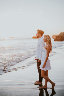 engagement photography photo shoot posed holding hands on the beach at sunset point dume malibu cali
