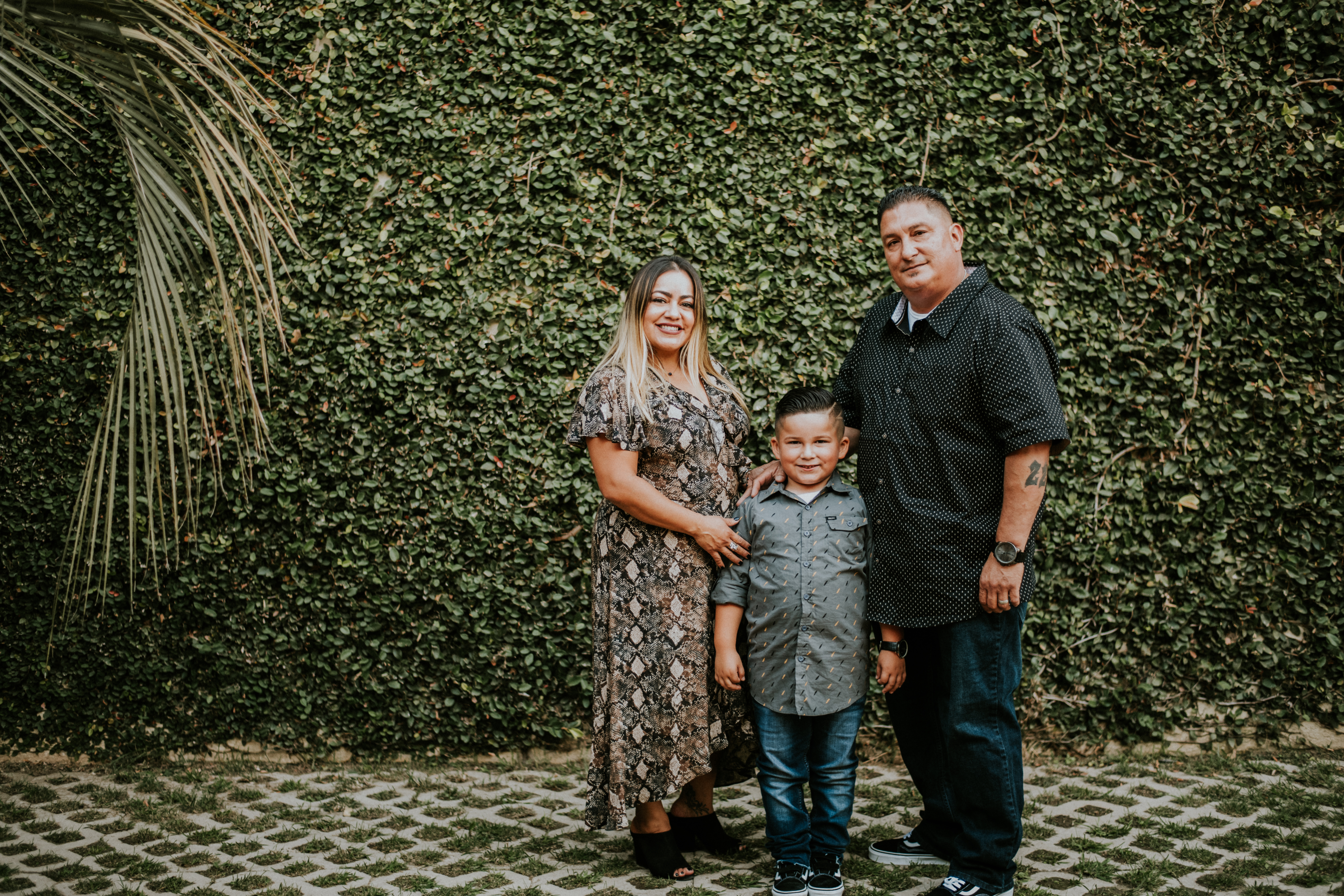 family posed in front of greenery wall family photography los angeles california