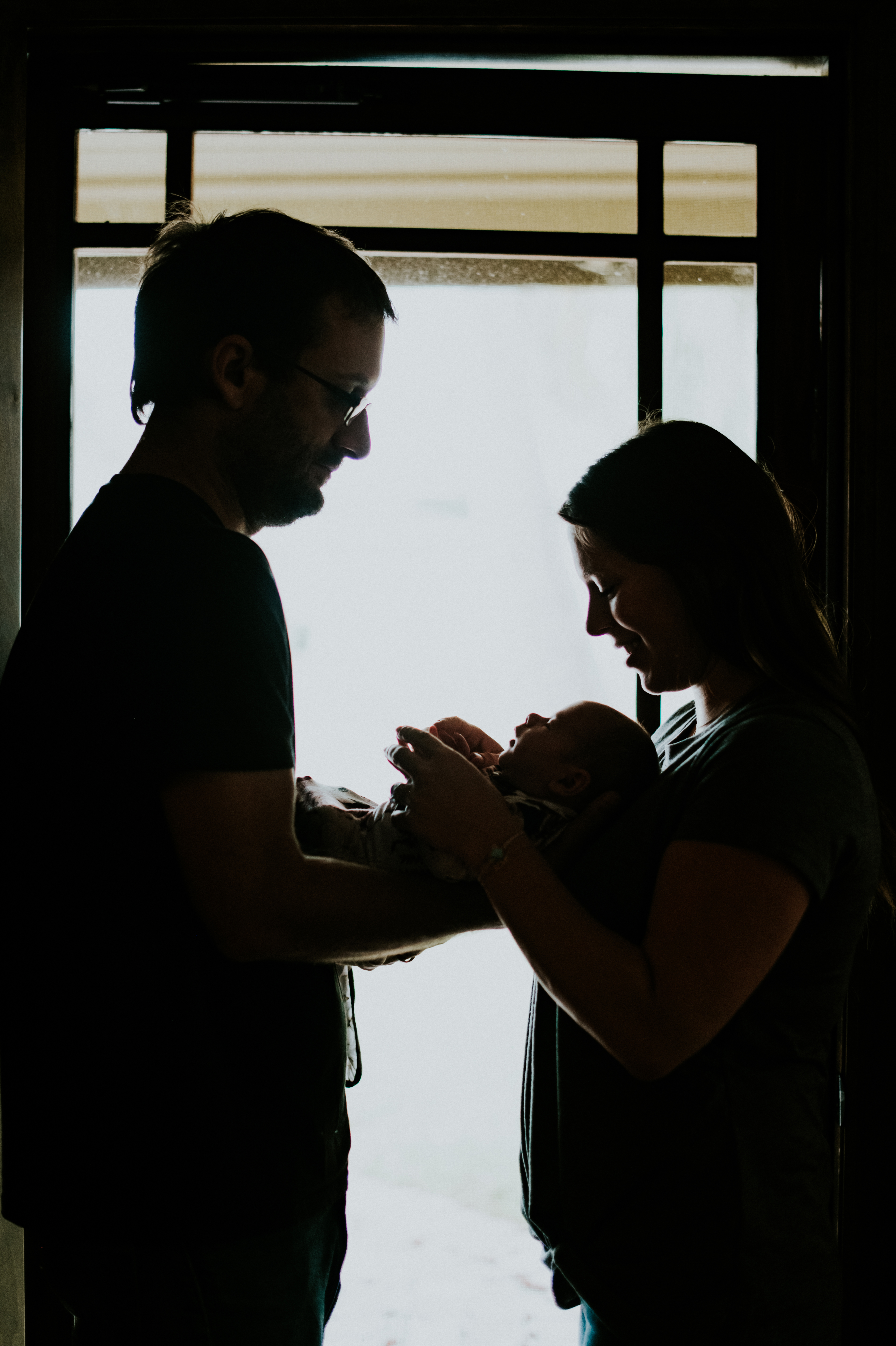 couple looking at baby silhouette at home lifestyle newborn photography los angeles california