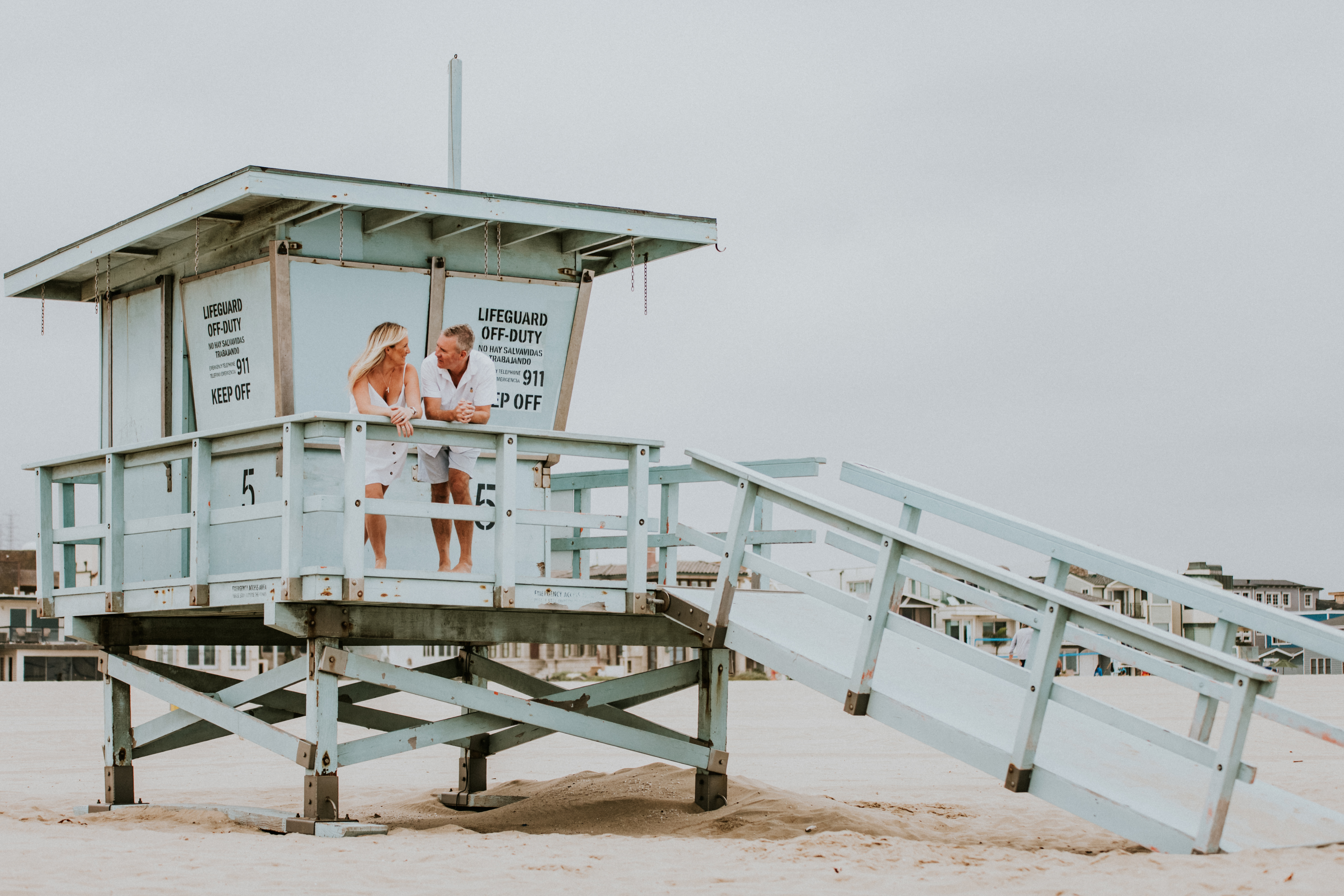 mom and dad posed on life guard tower on the beach family photography los angel