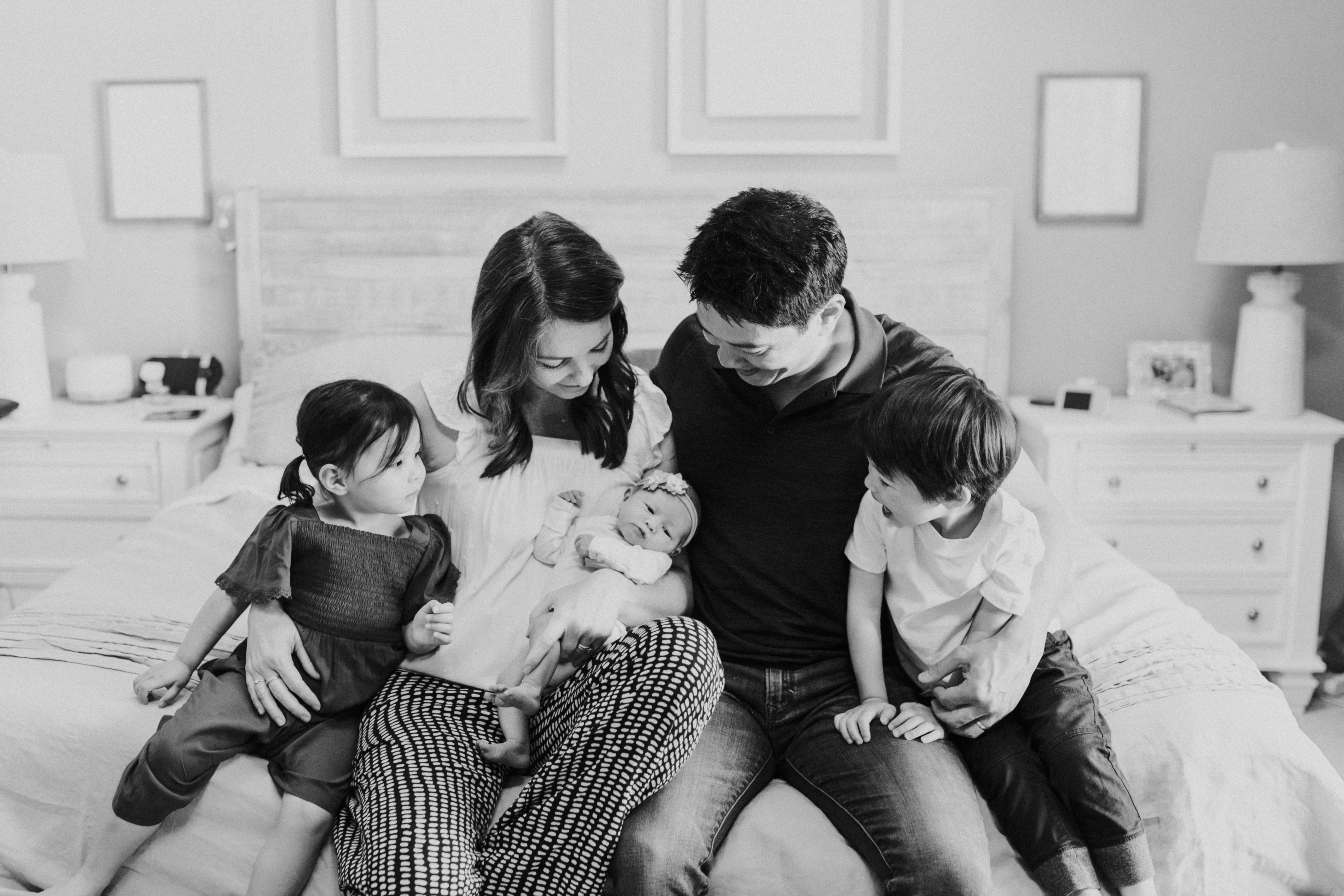 family looking at baby at home lifestyle newborn photography los angeles california