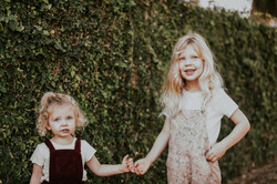 sisters holding hands in front of ivy wall family photography los angeles california