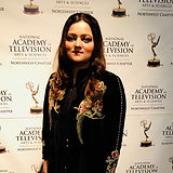 """Humaira Abid standing in front of a step-and-repeat that reads """"National Acadmy of Television Arts & Sciences Northwest Chapter"""""""