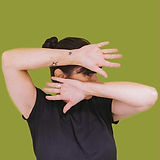Heather Dwyer looking to th sid with her hands covering parts of her face in front of a green background