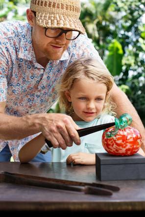 Instructor Helping Studen make a glass pumpkin