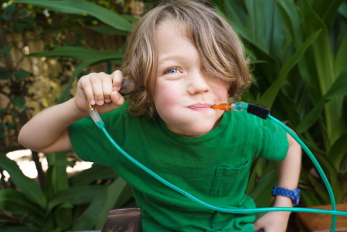 Kid Blowing into a Blowstraw