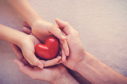 adult-and-child-hands-holiding-red-heart