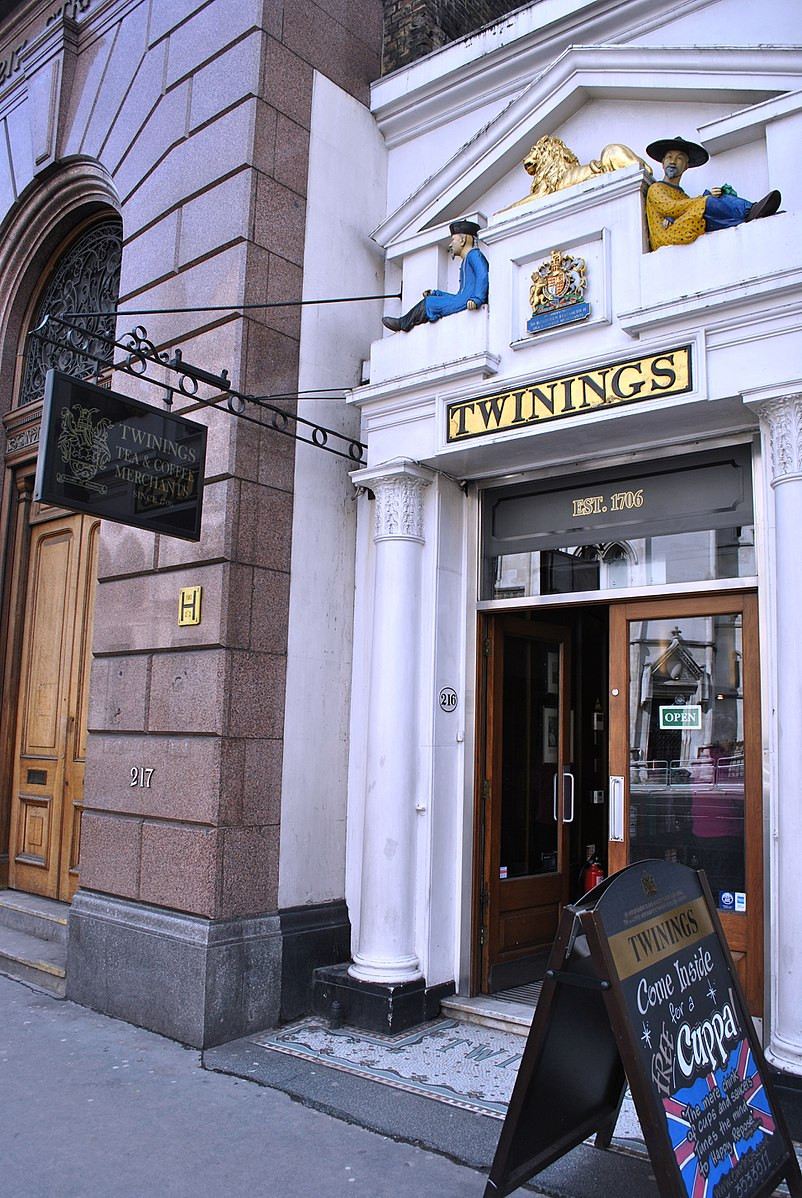 Front door to Twinings Tea Shop beneath golden lion statue and sign that says Est. 1706.