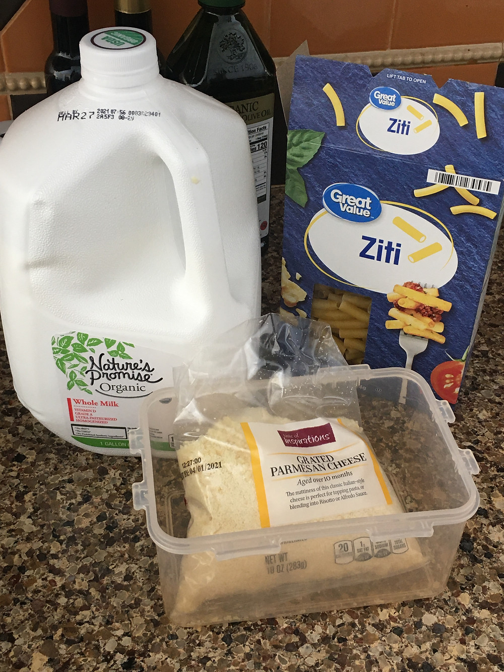 kitchen counter with one gallon of milk, one box of ziti pasta, one package of grated parmesan cheese