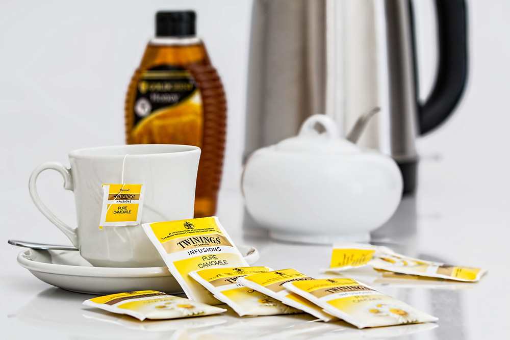 Yellow twining tea bags, white tea cup and saucer, with honey, sugar bowl, and kettle in background.