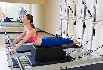 Women stretching on pilates reformer.Pilates Equipment Maintenance in Broward, Palm Beach
