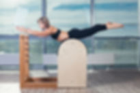 Woman stretching on pilates ladder barrel. Pilates and Gyrotonic Equipment Service and Maintenance, gyrotonic equipment assembly, gyrotonic equipment repair