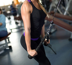 Woman doing tricep pulls at gym.Fitness Strength Equipment Cable Repair