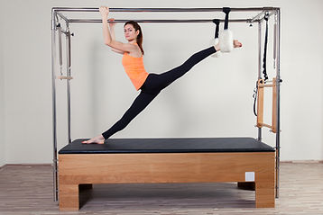 Woman stretching on Pilates cadillac.Pilates Equipment Repair and Service