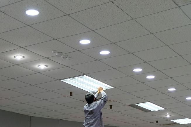 Maintenance man changing light bulbs in